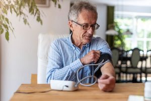 Man Putting on Blood Pressure Cuff for RPM